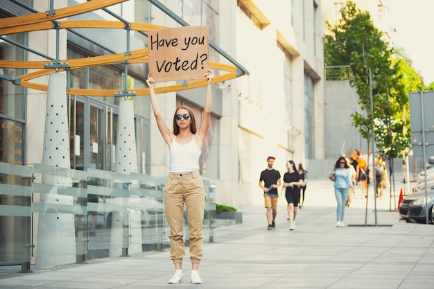 투표하셨나요? 표지판이 있는 친구 - 여자는 그녀를 짜증나게 하는 것에 항의합니다. 표지판이 있는 거리에서 자유롭게 말할 수 있는 솔로 데모. 대중에게 들은 의견. 사회 생활, 정치, 평등.