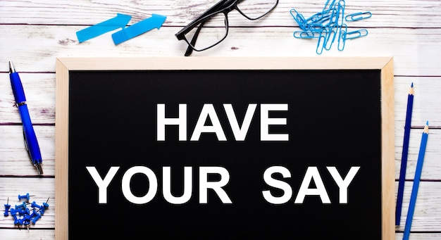 Have your say written on a black note-board next to blue paper clips, pencils and a pen