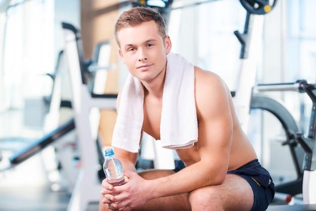 운동 후 휴식입니다. 물병을 들고 체육관에서 휴식을 취하는 동안 카메라를 바라보는 잘생긴 젊은 근육질의 남자