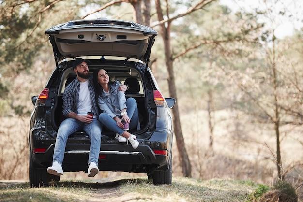 휴식. 자동차 뒷부분에 앉는다. 자연을 즐기고 있습니다. 부부가 새 검은 차를 타고 숲에 도착했습니다.