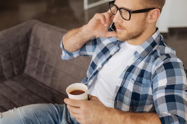 休憩。ソファに座ってお茶を飲みながら電話で話すスマートな素敵なひげを生やした男