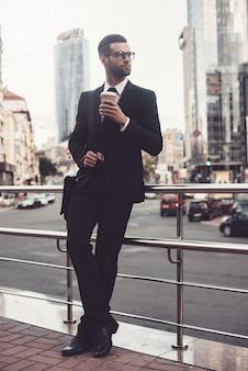 コーヒーブレイク。コーヒーカップを保持している完全なスーツで自信を持って若い男