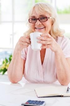 커피를 마시며 휴식을 취합니다. 테이블에 앉아 있는 동안 컵을 들고 카메라를 보며 웃고 있는 행복한 노년 여성