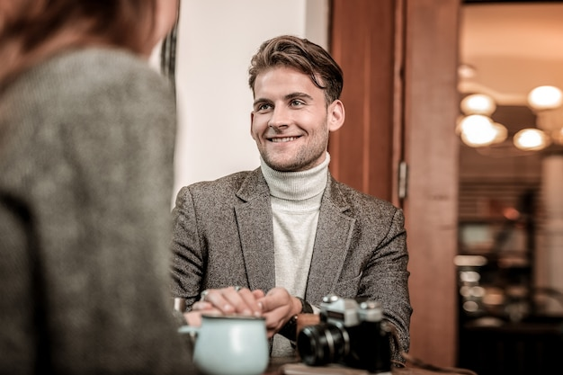 Разговор. улыбающийся мужчина разговаривает с женщиной в кафе