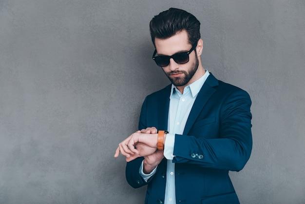 1時間でデートする。サングラスをかけ、灰色の背景に立っている間彼の腕時計を見ているハンサムな若い男
