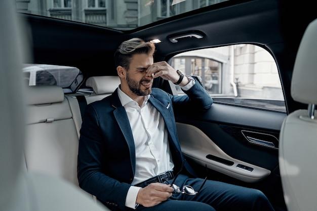 두통이 있다. 차에 앉아있는 동안 코를 마사지하고 눈을 감고 유지하는 formalwear에서 좌절 된 젊은 남자