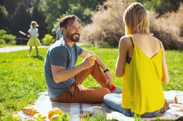 おやつを食べる。彼らの子供がバックグラウンドで遊んでいる間彼の妻と話しているハンサムなコンテンツの男