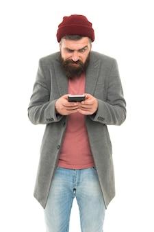 外出先でブログを持っている。スマートフォンから新しいブログ投稿を書いているひげを生やした男。プライベートブログを保持しているブロガー。モバイルデバイスのオンラインソーシャルネットワークまたはブログへの流行に敏感な投稿。