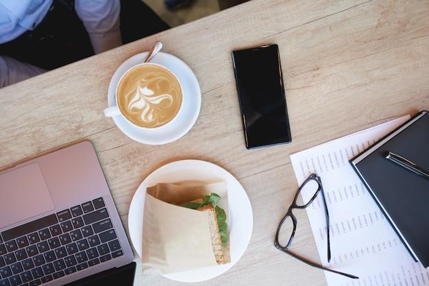 カフェの木製テーブルにコーヒーカプチーノサンドイッチラップトップとスマートフォンの朝食カップを持っています