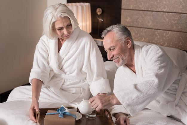 함께 아침을 먹고. 밝은 미소 세 커플 침대에 누워 기쁨을 표현하면서 아침을 먹고
