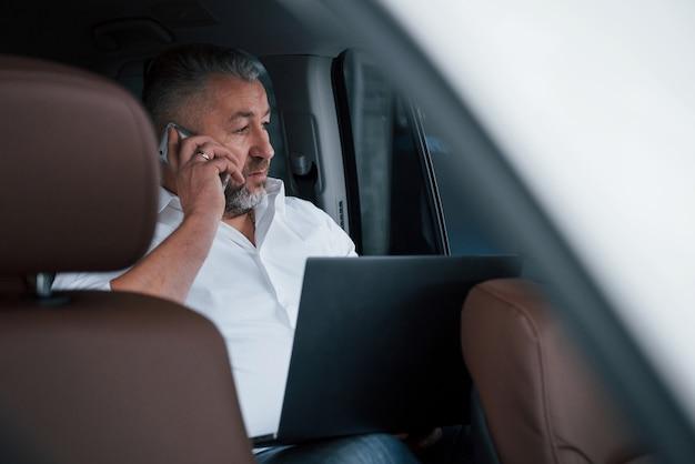 실버 컬러 노트북과 자동차의 뒤쪽에 앉아있는 동안 비즈니스 전화를 갖는