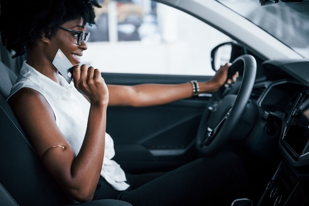 Having a call. young african american woman sits inside of new modern car.
