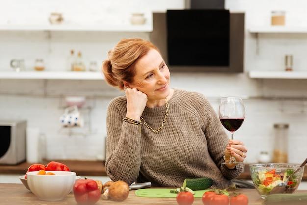 穏やかな夜を。一人でキッチンに滞在し、夕食のサラダを作りながらセーターを着ている楽しい生姜成熟した女性