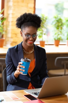 Having coffee break. cheerful curly interior designer having coffee break and reading e-mail on laptop