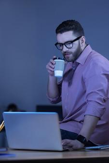 커피 마시고. 잘 생긴 심각한 수염 난된 남자가 테이블에 앉아 노트북 화면을 보면서 커피를 마시고