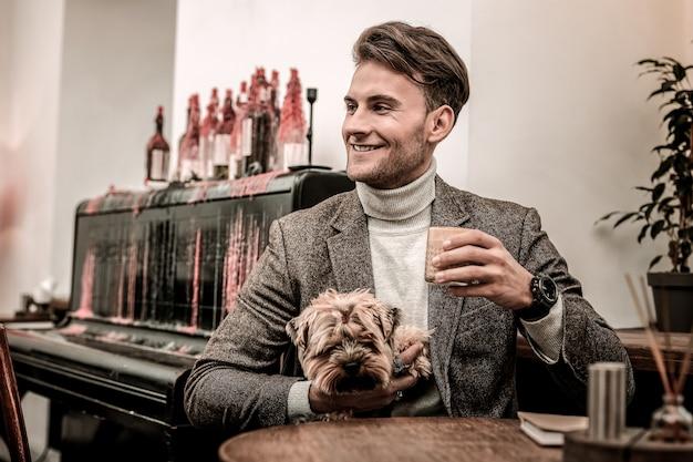 좋아하는 애완 동물과 커피를 마시고 있습니다. 개를 안고 커피를 마시는 남자