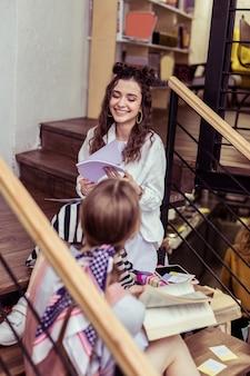 コミュニケーションをとる。彼女の明るい髪の友人が厚い本を読んでいる間、紙の束をめくっている暗い髪の晴れやかな女の子
