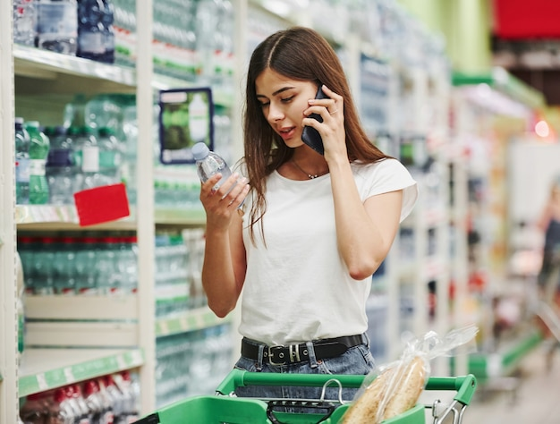 Having conversation by using phone. female shopper in casual clothes in market looking for products.