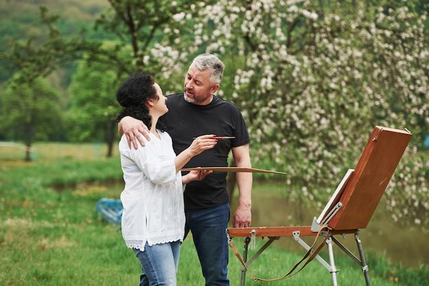 Беседа. пожилая пара отдыхает и вместе работает над краской в парке