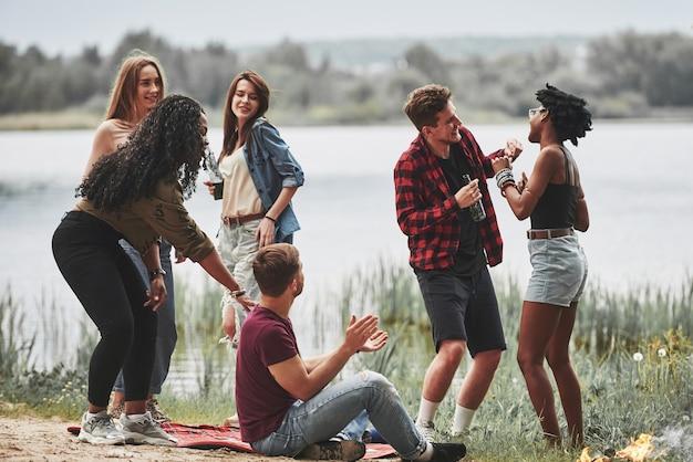 Разговаривают друг с другом. группа людей устраивает пикник на пляже. друзья веселятся в выходные.