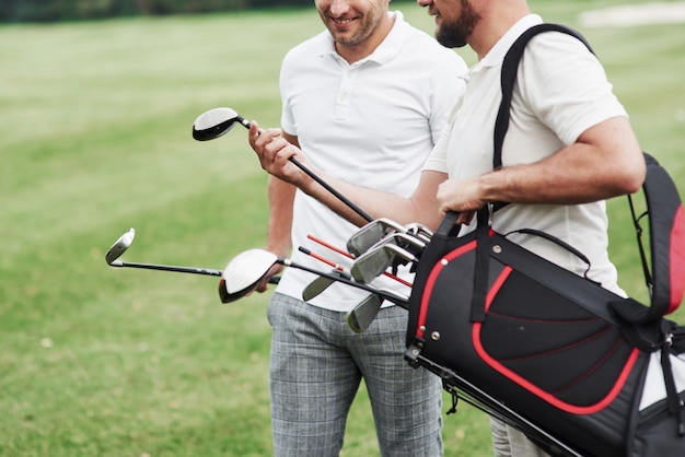 대화를 나누고 웃고 있습니다. 골프 장비와 스포츠 분야에 두 친구의 자른 된 사진.
