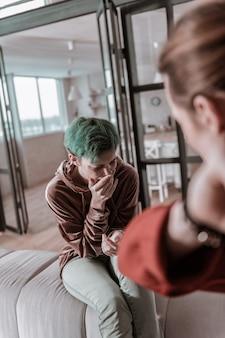 クレイジーな男がいる。狂った男を抱えて無力感を感じながらひどく泣いている若い緑髪の妻