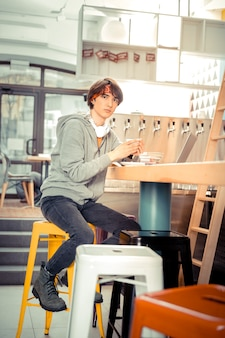Having a cup of coffee. a teenager sitting in the cafe with a cup of coffee