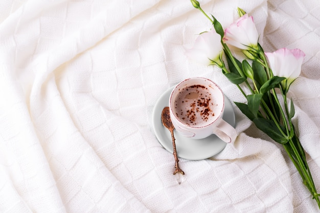 Having a cup of coffee with chocolate, flowers eustoma on blanket in bed.