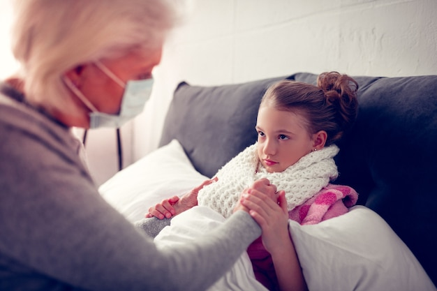 Having flue. cute dark-eyed girl wearing warm beige scarf while having flue looking at her caring granny