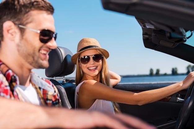 어디든 갈 수 있는 자유가 있습니다. 아름다운 젊은 여성이 남자 친구를 보고 웃고 있는 동안 컨버터블에서 도로 여행을 즐기는 아름다운 젊은 부부