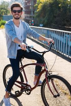 어디든 갈 수 있는 자유가 있습니다. 카메라를 보고 웃 고 자전거에 잘생긴 젊은 남자
