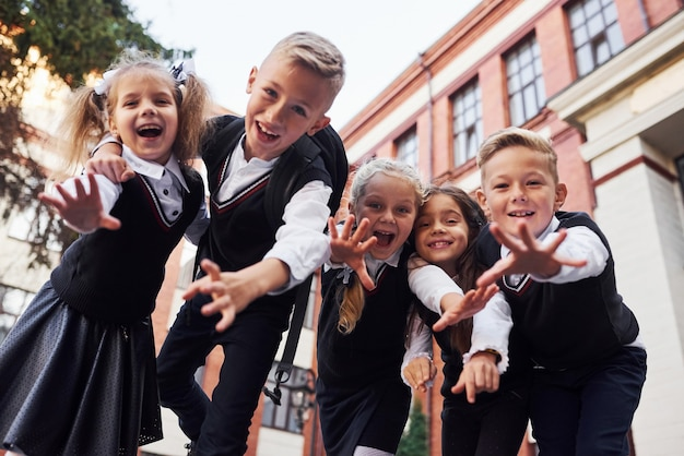楽しんで、お互いを受け入れます。教育棟の近くで一緒に屋外にある制服を着た子供たちのグループ。