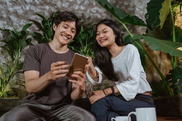 ガールフレンドと一緒にコーヒーショップで楽しんで、携帯電話を使用して、10代のカップルのコンセプト
