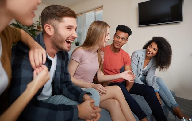 一緒に時間を楽しんでいるカジュアルな服装で若い幸せな多文化の人々の家のグループで楽しんでください