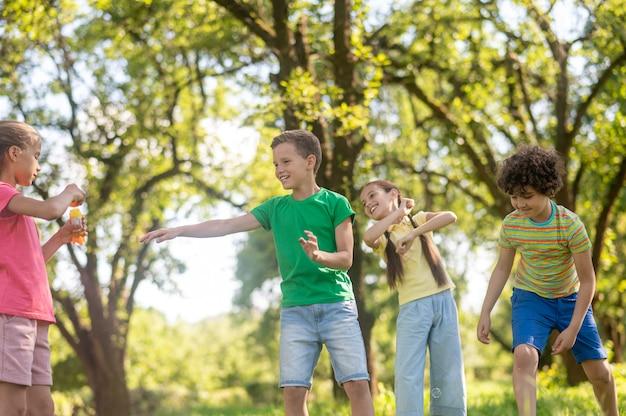 재미. 밝은 옷을 입고 녹색 공원 잔디밭에서 비누방울을 가지고 노는 쾌활한 행복한 학령기 소년 소녀들