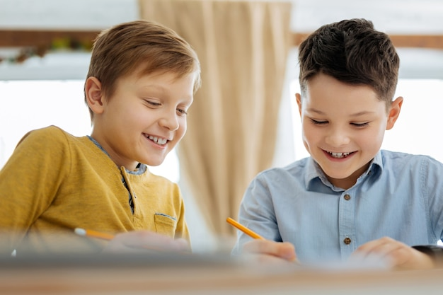 Having fun. cheerful pleasant pre-teen boys sitting at the table and drawing together while smiling and discussing the picture
