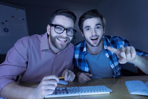 楽しんでください。テーブルに座って、コンピューターを使用しながら笑っている陽気な前向きなハンサムな男性