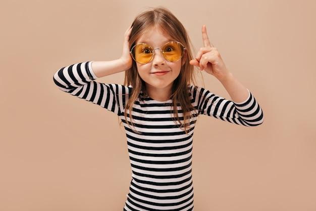 재미, 베이지 색 배경에 고립 된 즐거운 놀라운 어린 소녀의 진정한 긍정적 인 감정을 표현합니다.