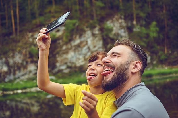 Веселиться. отец пример благородного человека. принимая селфи с сыном. ребенок катается на плечах папы. счастье быть отцом мальчика.