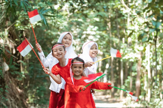 Having fun group of asian little girls holding the red and white flag and raised together the flag