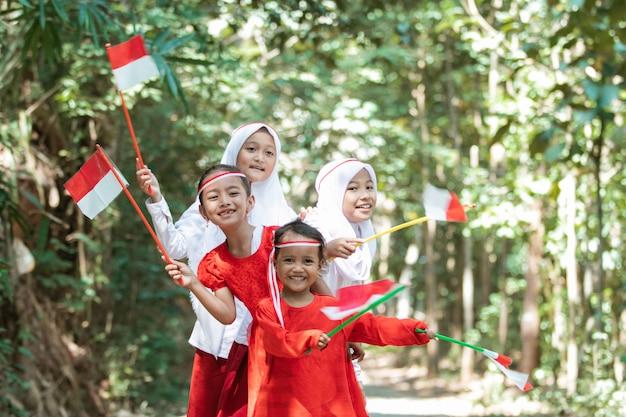 Веселая группа азиатских маленьких девочек держит красно-белый флаг и вместе подняла флаг