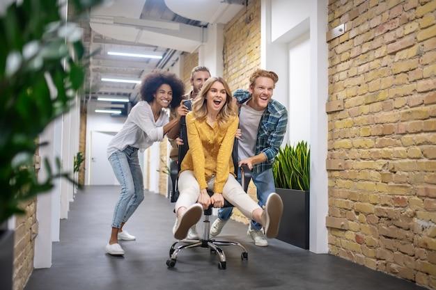 楽しんでください。天気の良い日を過ごした後、オフィスの廊下で椅子に乗る若者のグループ