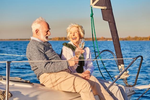 Веселая счастливая красивая старшая семейная пара пьет вино или шампанское и смеется во время