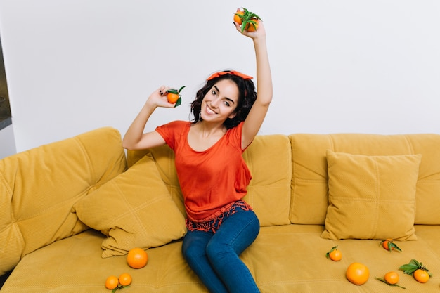 Having fun at home of amazing excited pretty young woman with brunette cut curly hair smiling on orange couch among tangerines in living room.