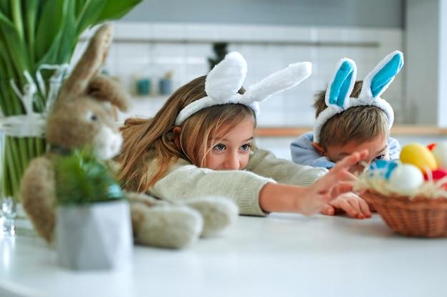 부활절 달걀 사냥에 재미. 어린 소년과 소녀 토끼 귀를 입고 계란 바구니에 손을 당깁니다. 사랑스러운 아이들은 집에서 부활절을 축하합니다.