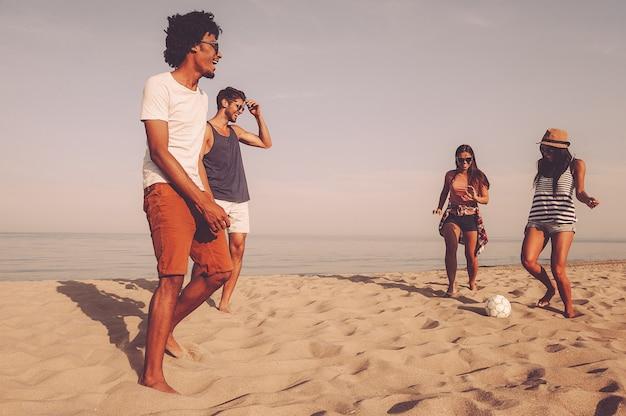 ビーチで楽しんでください。海を背景にビーチでサッカーボールで遊ぶ陽気な若者のグループ