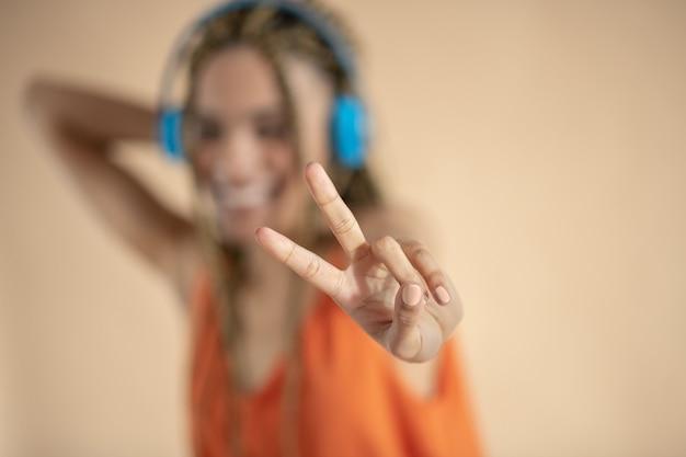 楽しんでください。青いヘッドフォンで若いアフリカ系アメリカ人女性の笑顔、音楽を聴いて、ピースサインを表示