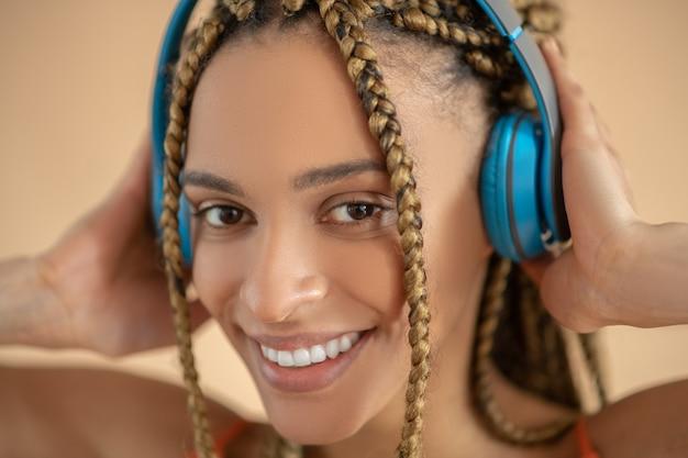 楽しんでください。青いヘッドフォンに触れて、音楽を聴いて、若いアフリカ系アメリカ人女性の笑顔
