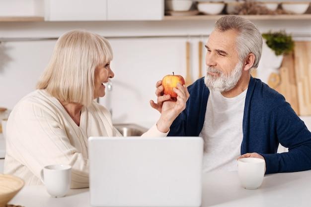 一緒に楽しんでください。ラップトップの前に家で座って、愛を表現し、お互いを見ながらリンゴを持っている魅力的な楽しい老夫婦