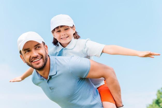 一緒に楽しんでください。屋外に立っている間彼の息子を肩に乗せて陽気な若い男